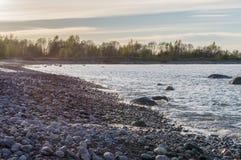 Costa costa del guijarro del mar Báltico en la puesta del sol Imagen de archivo