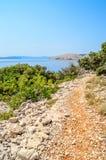Costa costa rocosa con una trayectoria y los arbustos del pie y árboles por el efecto negativo del medicamento Imágenes de archivo libres de regalías