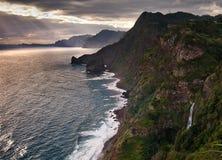 Costa costa rocosa de Madeira con las cascadas, la onda y la puesta del sol imagen de archivo