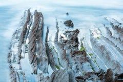 Costa crepuscular do oceano com a rocha stratiform com nervuras Fotos de Stock Royalty Free