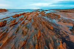 Costa crepuscular do oceano com a rocha stratiform com nervuras Imagem de Stock