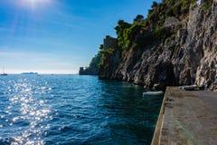 Costa de Amalfi com costa rochosa e barco pelo cais no mar Mediterrâneo, Positano foto de stock
