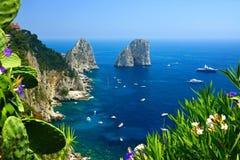 Costa de Capri com rochas de Faraglioni, flores e barcos, Itália imagem de stock