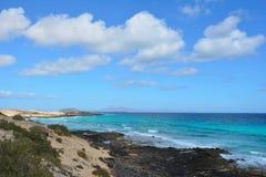 Costa de Corralejo, Fuerteventura, España Océano de la turquesa y cielo azul nublado imagen de archivo