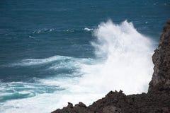 A costa de mar áspero com as ondas que chrashing contra a lava preta balança Foto de Stock
