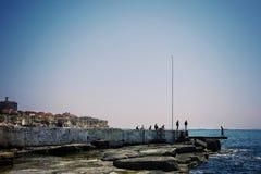 Costa de mar Cáspio com rochas e as construções distantes da cidade imagem de stock royalty free