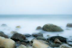 Costa de mar con las rocas y las ondas en la falta de definición de movimiento imagen de archivo