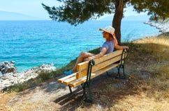 Costa de mar del verano con la mujer en el banco (Grecia) Foto de archivo libre de regalías