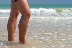 Costa de mar de passeio dos troncos de natação do close-up dos pés do homem novo, água do horizonte da onda Foto de Stock Royalty Free