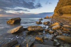 Costa de mar rochosa, à vista do sol de aumentação foto de stock royalty free
