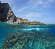 Costa de mar rochosa acima e abaixo da água com peixes imagens de stock