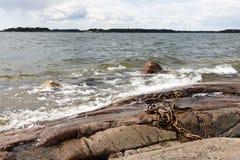 Costa de mar rochosa e ondas de água espumosas Fotos de Stock Royalty Free
