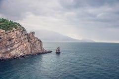 Costa de mar rocosa en día lluvioso nublado la roca parece ratón con queso Cielo gris con lluvia en horizonte fotografía de archivo
