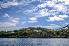 Costa de Noruega com as casas de campo encantadores no fundo, verão, s Imagem de Stock Royalty Free
