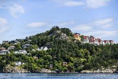 Costa de Noruega com as casas de campo encantadores no fundo, verão, s Fotos de Stock Royalty Free