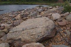 Costa de piedra hermosa del río detrás de un círculo polar Imagen de archivo