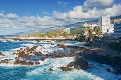 Costa de Puerto de la Cruz, de Tenerife, de Ilhas Canárias - Oceano Atlântico e peça moderna da cidade com hotéis e recursos turi fotografia de stock