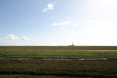 Costa del Mare del Nord del tedesco con il faro sull'orizzonte distante Fotografie Stock