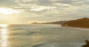 Costa costa del océano con las personas que practica surf en luz de la puesta del sol Imagen de archivo libre de regalías