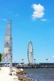 Costa del río Potomac y un embarcadero con Ferris debajo del cielo azul del verano Fotografía de archivo