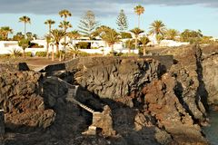 Costa del Silencio - high volcanic coast with rock formation. In the Silence Bay with palm trees at the background Royalty Free Stock Image