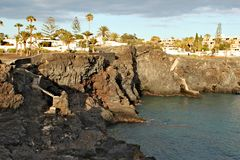 Costa del Silencio - high volcanic coast with rock formation. In the Silence Bay with palm trees at the background Stock Photography