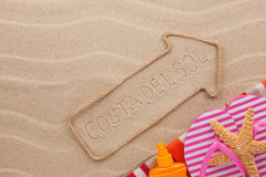 Costa del Sol pointer and beach accessories lying on the sand Royalty Free Stock Photography