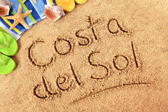 Costa del Sol. The words Costa del Sol written on a sandy beach with beach towel, starfish and flip flops stock images