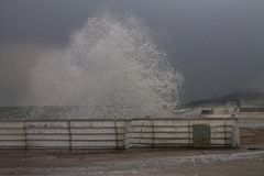 Costa di inverno, un'onda che si schianta nell'inferriata della banchina Fotografia Stock