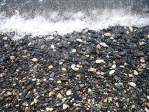 Costa di mare, ciottolo ed onda di schiumatura rashing Immagine Stock