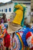 Costa do cabo, Gana - 15 de fevereiro de 2014: Dançarino mascarado e trajado colorido durante festividades africanas do carnaval Fotografia de Stock