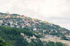 A costa do Mar Negro, montes verdes com casas, azul nubla-se o céu Fotografia de Stock Royalty Free