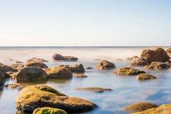 Costa Dreamlike de um mar com pedras musgosos fotografia de stock royalty free