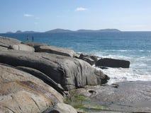 Costa e spiaggia rocciose australiane con le rocce giganti e le piante indigene Immagine Stock