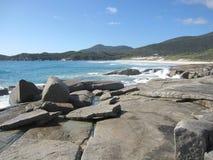 Costa e spiaggia rocciose australiane con le rocce giganti e le piante indigene Immagine Stock Libera da Diritti