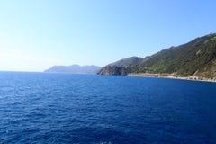 Costa e vila Corniglia de Cinque Terre e mar Mediterrâneo rochosos Fotografia de Stock Royalty Free