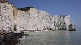 Costa inglesa bonita Seaford Sussex do leste Inglaterra Reino Unido com os penhascos de giz brancos, as ondas e o céu azul video estoque