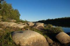 Costa pedregosa hermosa del río septentrional por la tarde Foto de archivo