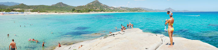 Costa Rei, Italy - August 25: Unidentified people in beach. Called Scoglio di Peppino. Panoramic view, sunny day in summertime, crystal water like a natural Royalty Free Stock Image