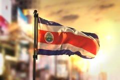 Costa Rica Flag Against City Blurred-Achtergrond bij Zonsopgang Backl Royalty-vrije Stock Afbeeldingen