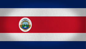 Costa Rica flag. With blue withe and red stripes in it and his little logo in the left center side, fabric texture background vignette Royalty Free Stock Photo