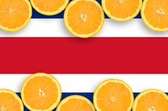 Costa Rica flag in citrus fruit slices horizontal frame. Costa Rica flag in horizontal frame of orange citrus fruit slices. Concept of growing as well as import stock photos