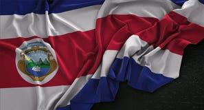 Costa Rica Flag Wrinkled On Dark-3D de Achtergrond geeft terug Stock Afbeeldingen