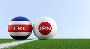 Costa Rica vs Japonia mecz piłkarski - piłek nożnych piłki w Costa Rica i Japonia krajowych kolorach na boisko do piłki nożnej Zdjęcia Stock