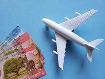 Costa Rican-Banknoten, weißes Plastikflugzeug und blauer Hintergrund lizenzfreies stockbild