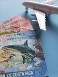 Costa Rican-Banknoten, weißes Plastikflugzeug und blauer Hintergrund stockfotos