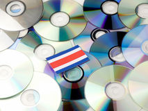 Costa Rican flag on top of CD and DVD pile isolated on white. Costa Rican flag on top of CD and DVD pile isolated Royalty Free Stock Image