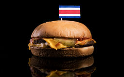Costa Rican flag on top of hamburger isolated on black Stock Photos