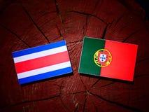 Costa Rican flagga med den portugisiska flaggan på en isolerad trädstubbe royaltyfri foto