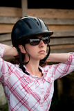 Costa Rican tourist putting on equestrian helmet Royalty Free Stock Photos